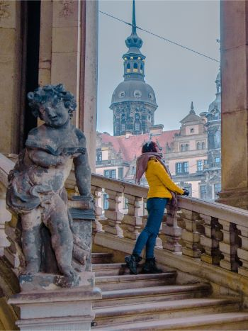 woman standing on stairs at the Dresden Zwinger with the tower of Dresden Castle in the distance